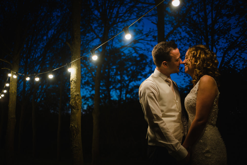 a bride and groom kiss under festoons at shushtoke barn