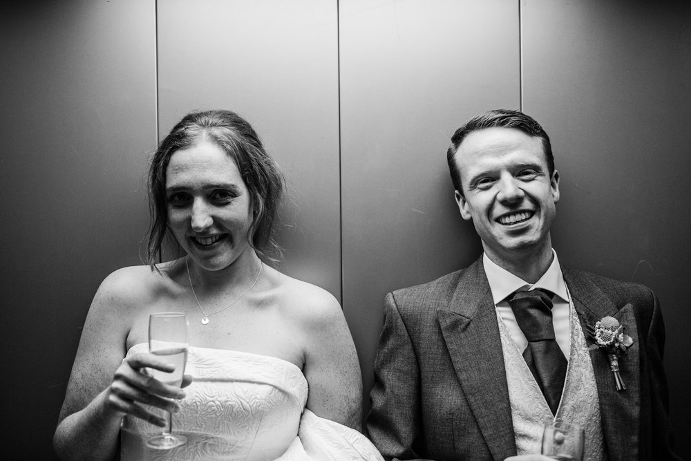 a bride and groom laugh in a lift at quarry bank
