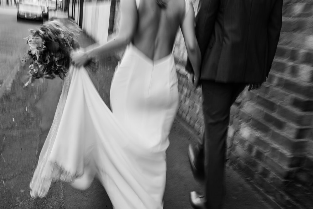 a bride and groom walk down the street the image is out of focus