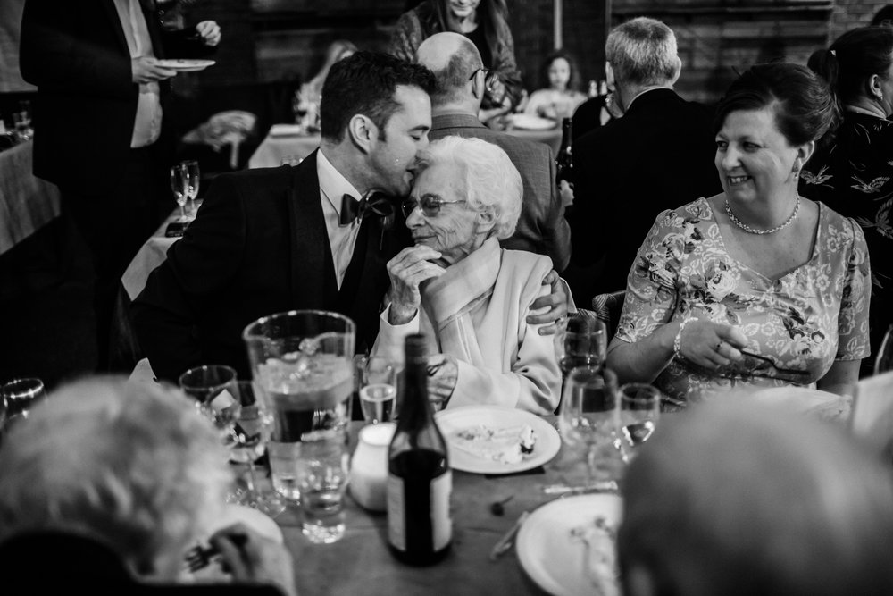a groom kisses his grandma at a wedding