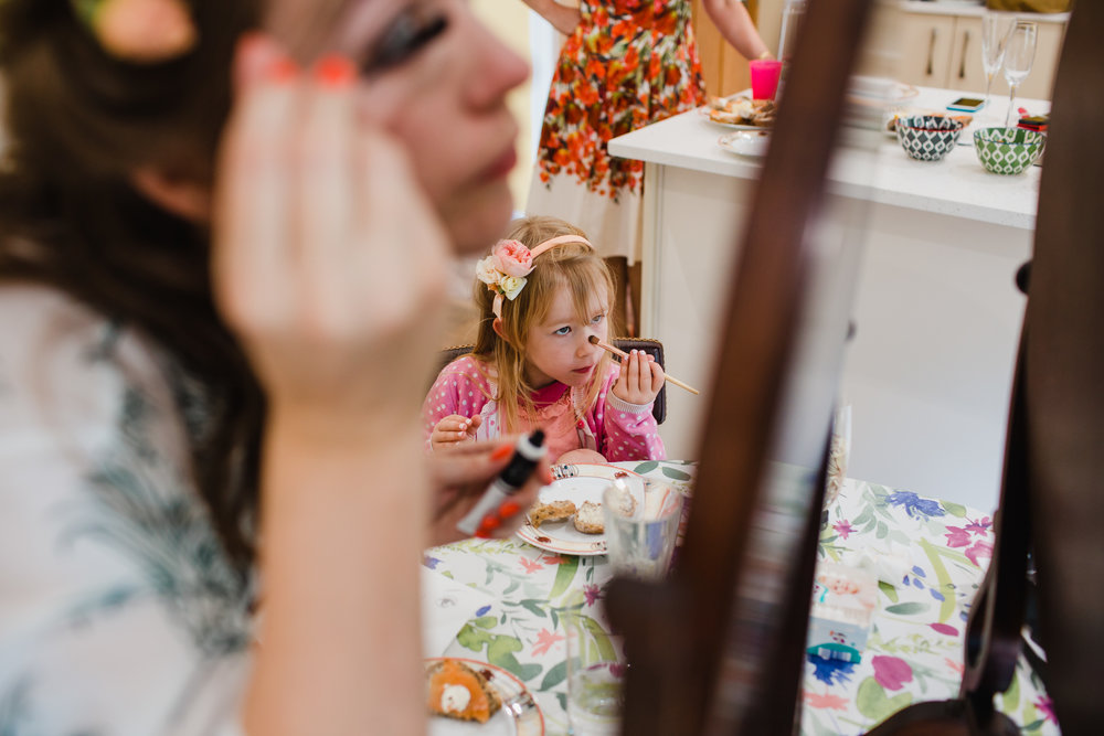 a flower girl copies the bride while putting on make up