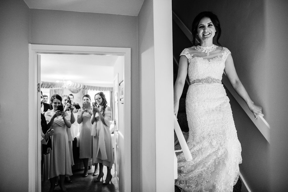 a bride comes down the stairs while her bridesmaids wait for her with phones out