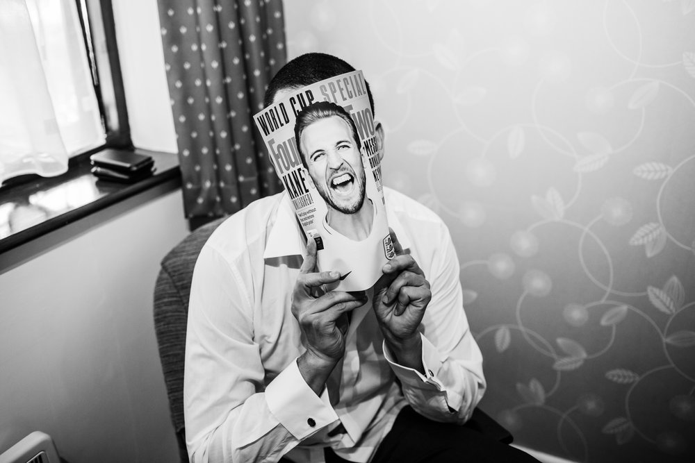a groomsman hiding behind a magazine before a wedding