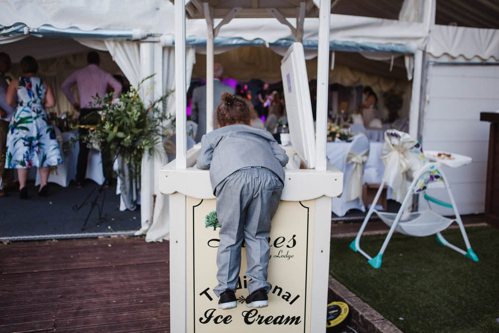 a child climbs into an ice cream freezer at a wedding