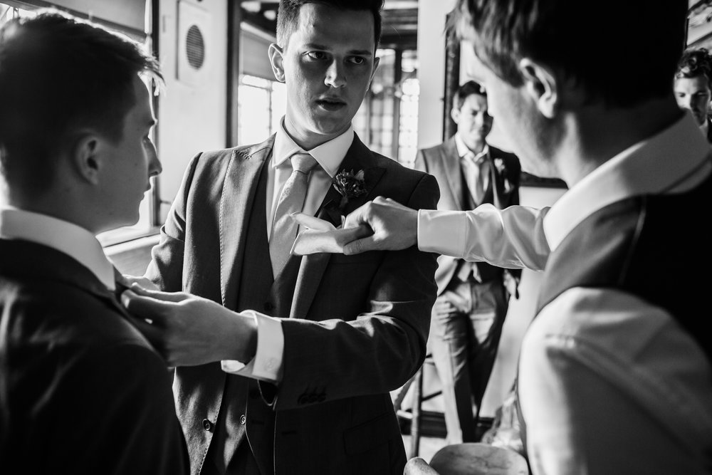 The groom has his flower attached before his wedding.