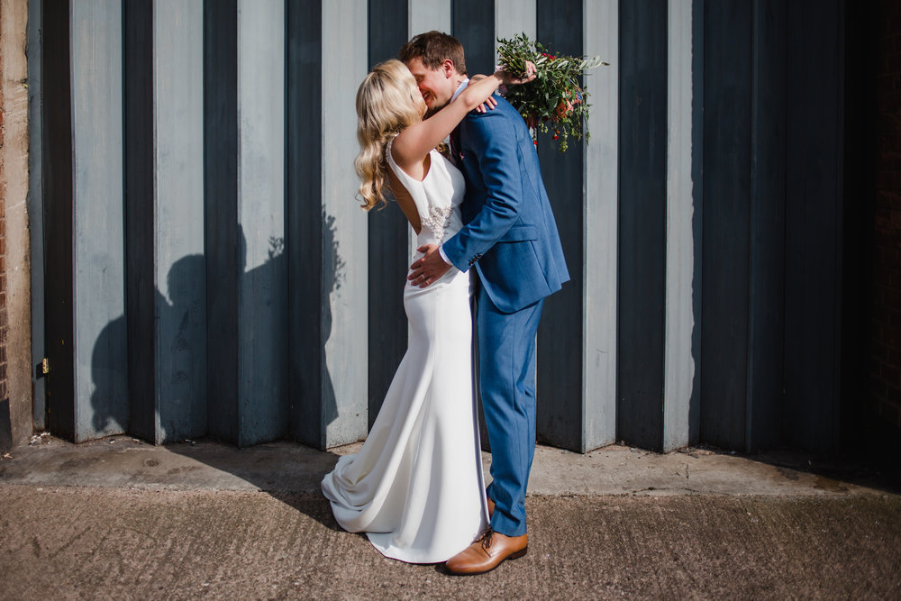 a bride and groom kiss in front of an industrial shutter door in digbeth Birmingham