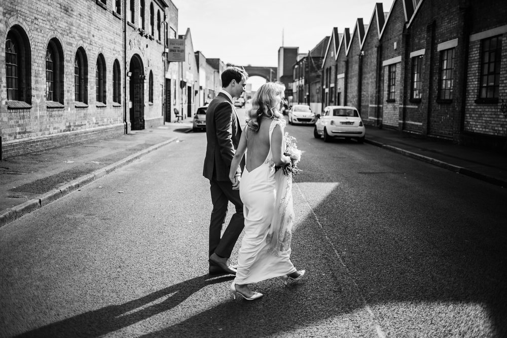 a bride and groom walk through the streets of digbeth