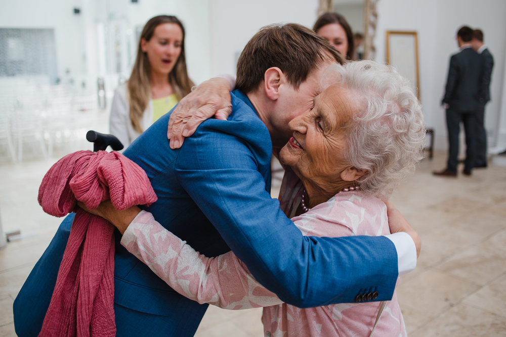 grandma gets a hug from the groom at a wedding at fazeley studios.