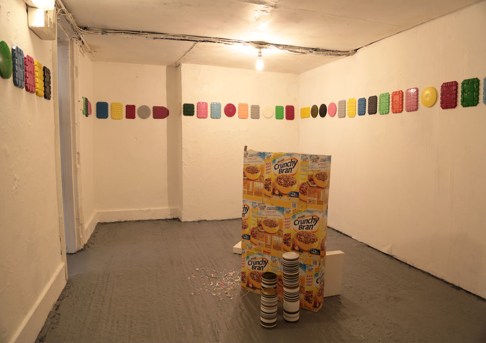 Border, Crunchy Bran Sculpture, Spill, Casts and Tiny towers   Mixed media, dimensions variable  In 'Border', casts were taken from food containers and arranged arbitrarily to form a picture border for the room.   In 'Crunchy Bran', our favourite cereal packaging is reconfigured and filled with peripherals from the collection.  In 'Spill', the peripherals spill out onto the floor  In 'Casts', plaster casts were made from crunchy bran cereal boxes. Some of the boxes feature enlarged print registration marks normally hidden but now made explicit on the surface  In 'Tiny Towers', tiny towers were made from collected coffee cup lids