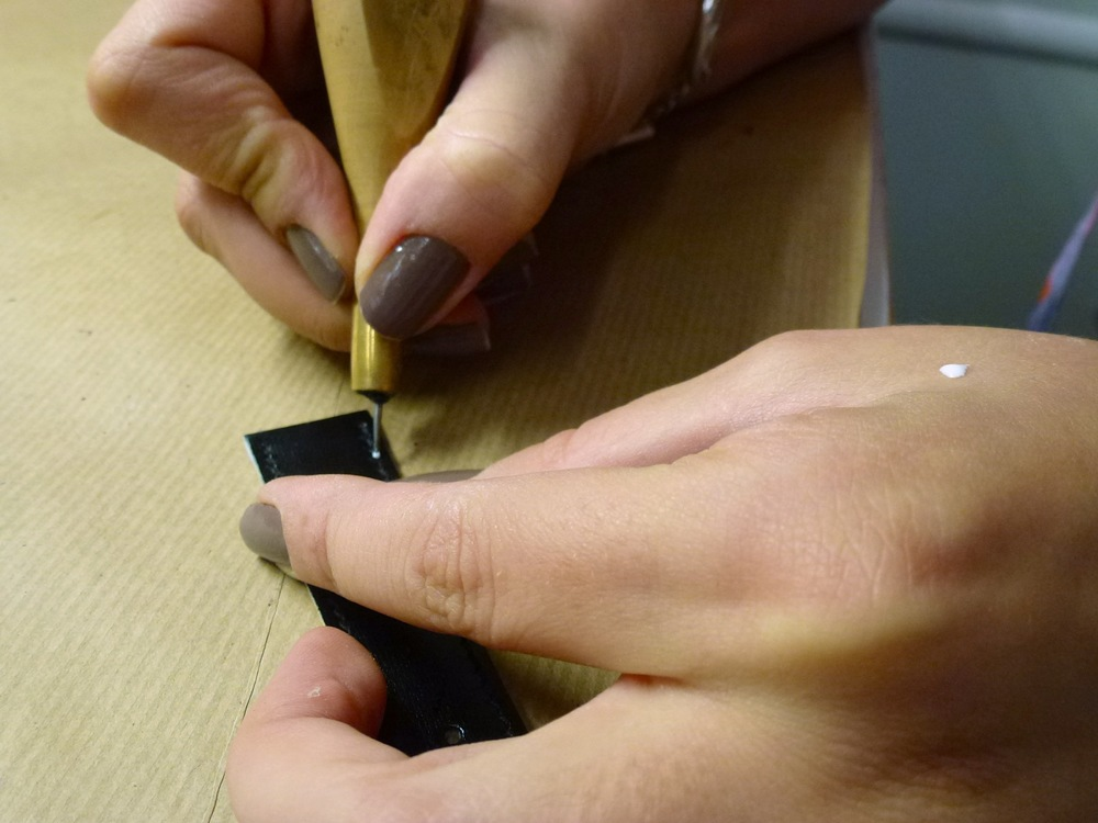 Delia Ionescu fixes the stitches with just the right amount of glue.