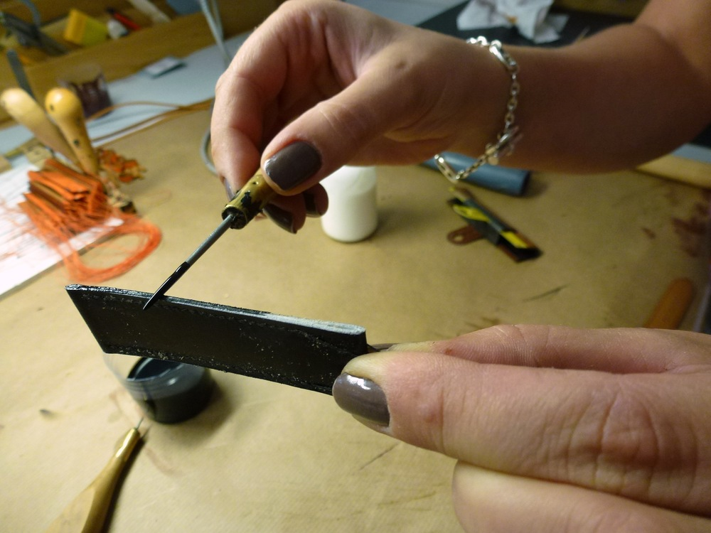 Delia Ionescu applies black dye to the sides of the strap before fixing and beveling it.