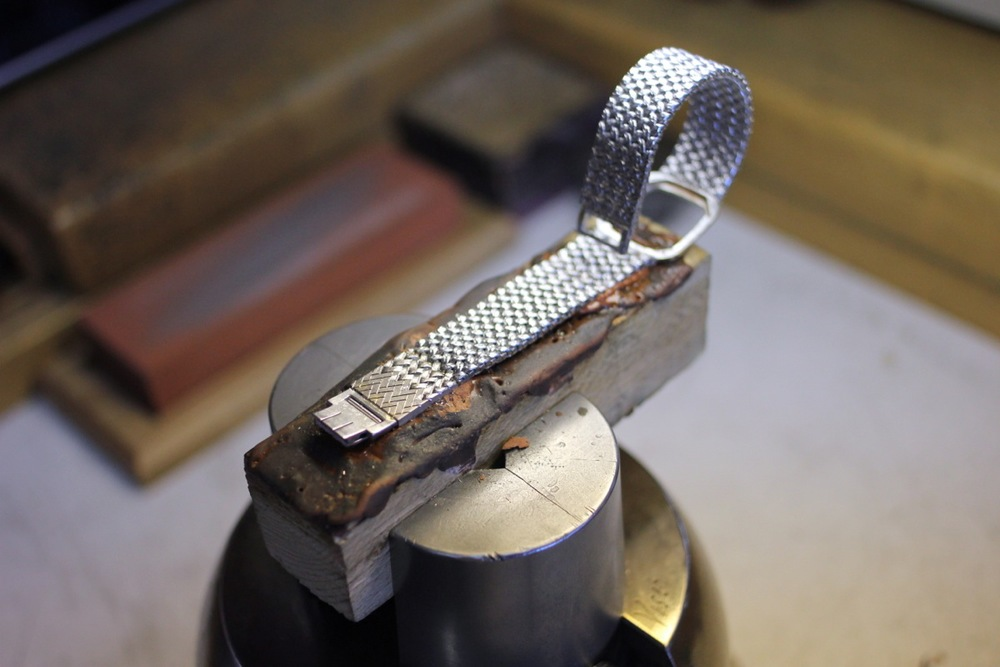 A vintage woven bracelet has a solid extension added, which is being hand-engraved to look exactly like the original weave