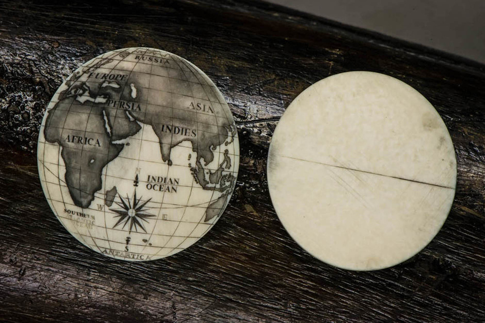 A finished scrimshaw dial next to the raw mammoth ivory blank