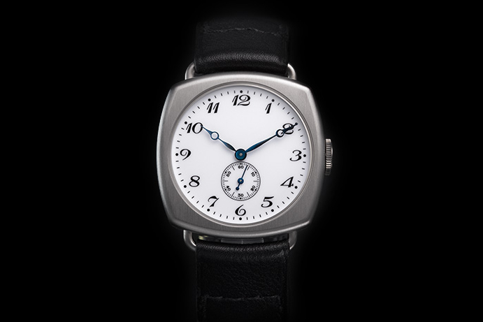 A white enamel dial offsets stylized Arabic numerals and blued style Breguet-style hands.