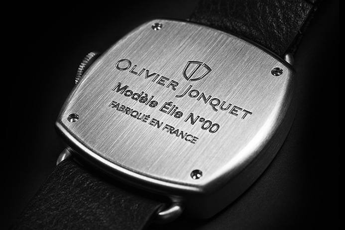 The brand name is engraved on the solid case back, leaving the dial unadorned to focus on overall design.