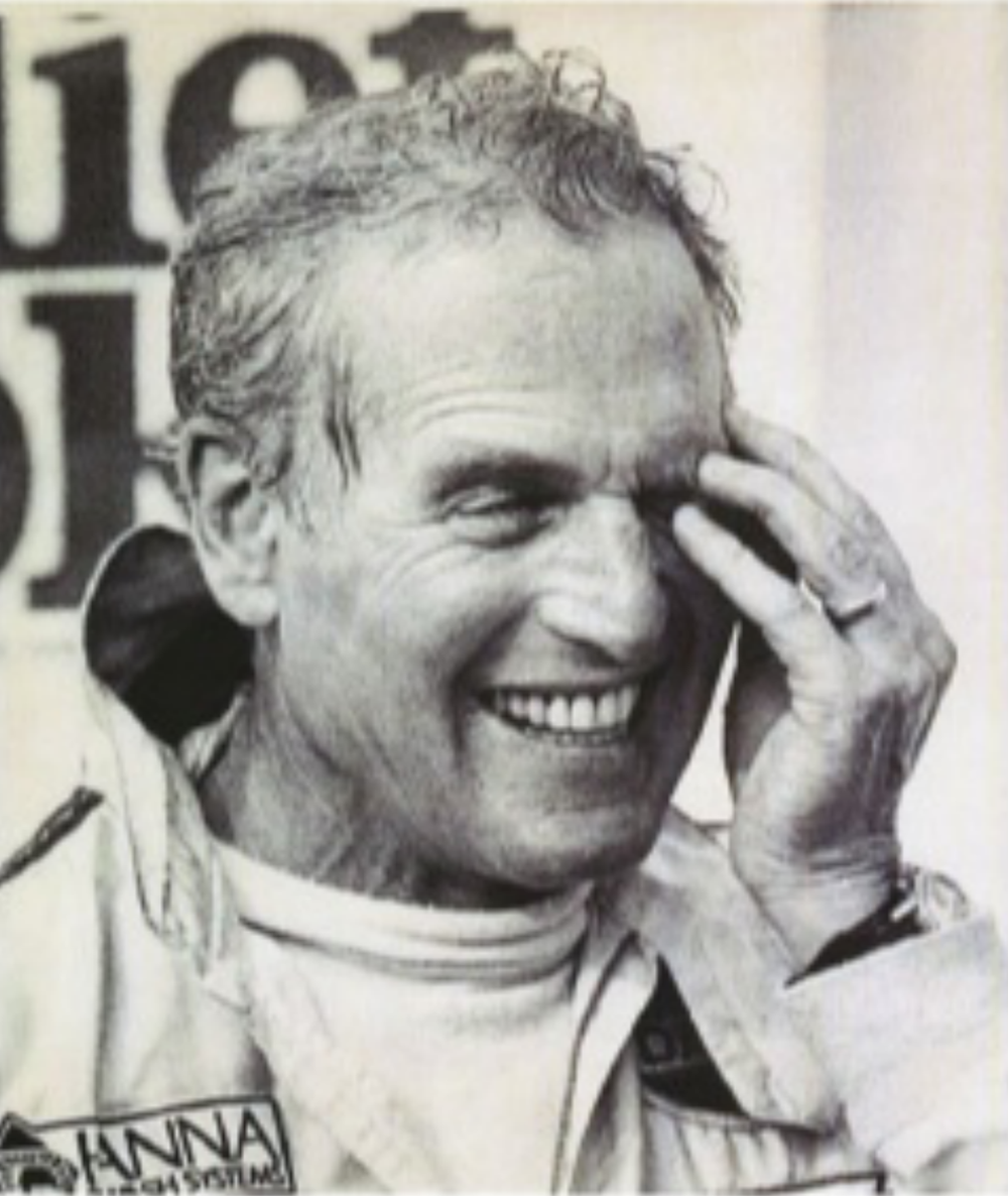 """Paul Newman in a similar racing suit with a """"Hanna Car Wash Systems"""" emblem on the dial, but no """"P.L. Newman"""" embroidery above it, wearing a Rolex Paul Newman Daytona."""