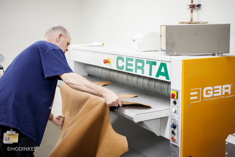 The leather is fed into a machine that evens surface thickness.