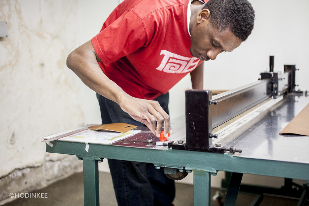 An employee adjusts the cutting table's blade.