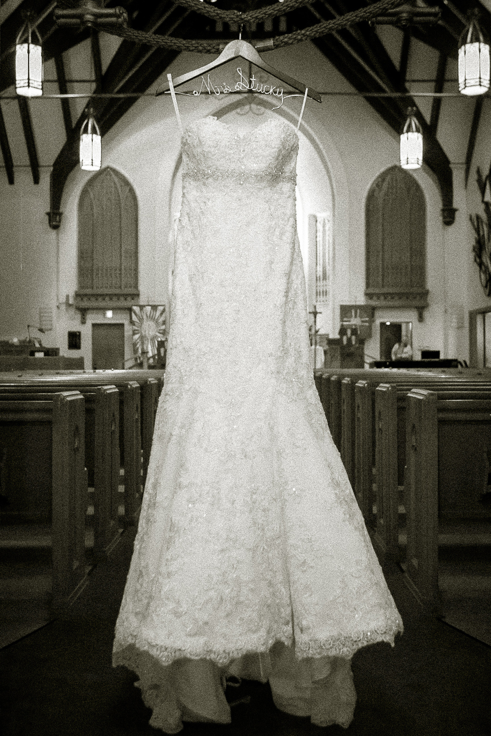 The wedding dress hanging at the entrance to the church sets the scene.
