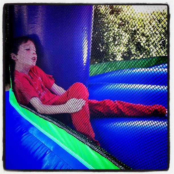 Leighton thru the netting of the bounce house. He likes red. (Taken with instagram)
