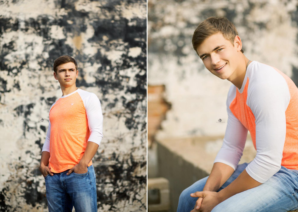 blonde senior guy in a electric orange and white baseball tee in front of an erroded black and white wall