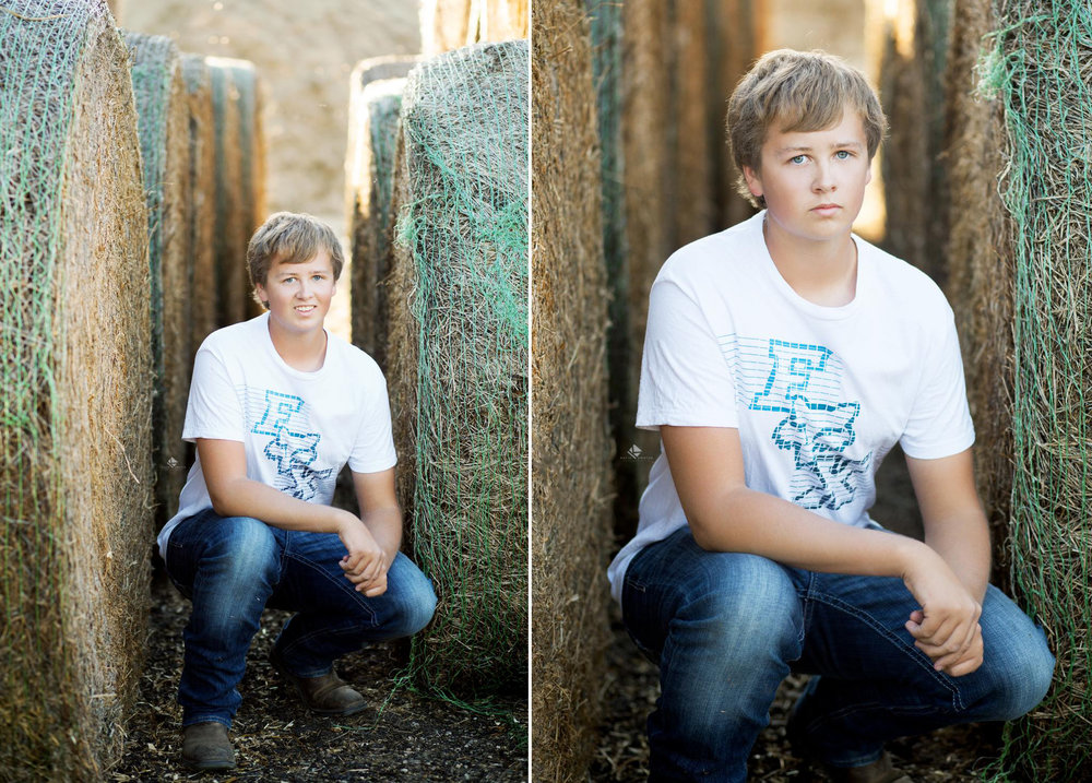 Blonde senior boy in a white t shirt and jeans squatting in between hay bales