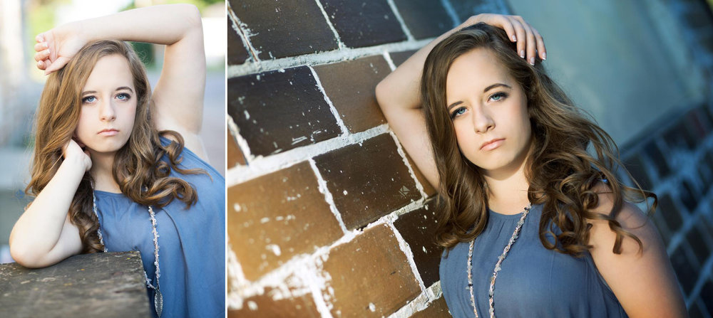 brunette senior girl in a blue top leaning against a brick building