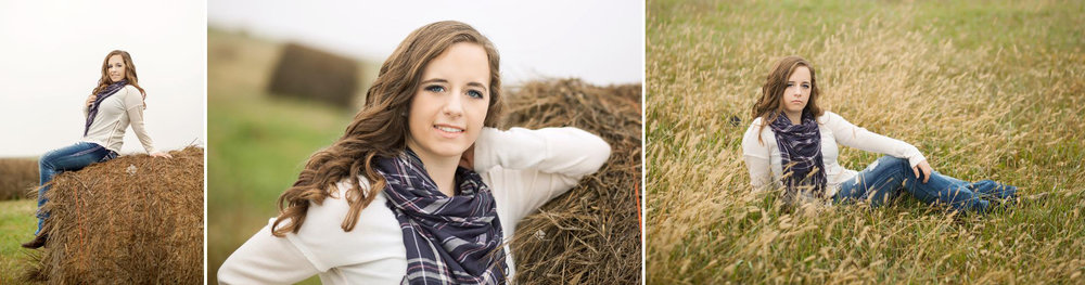 brunette senior girl in a white sweater with a navy scarf sitting in a field and on a haybale