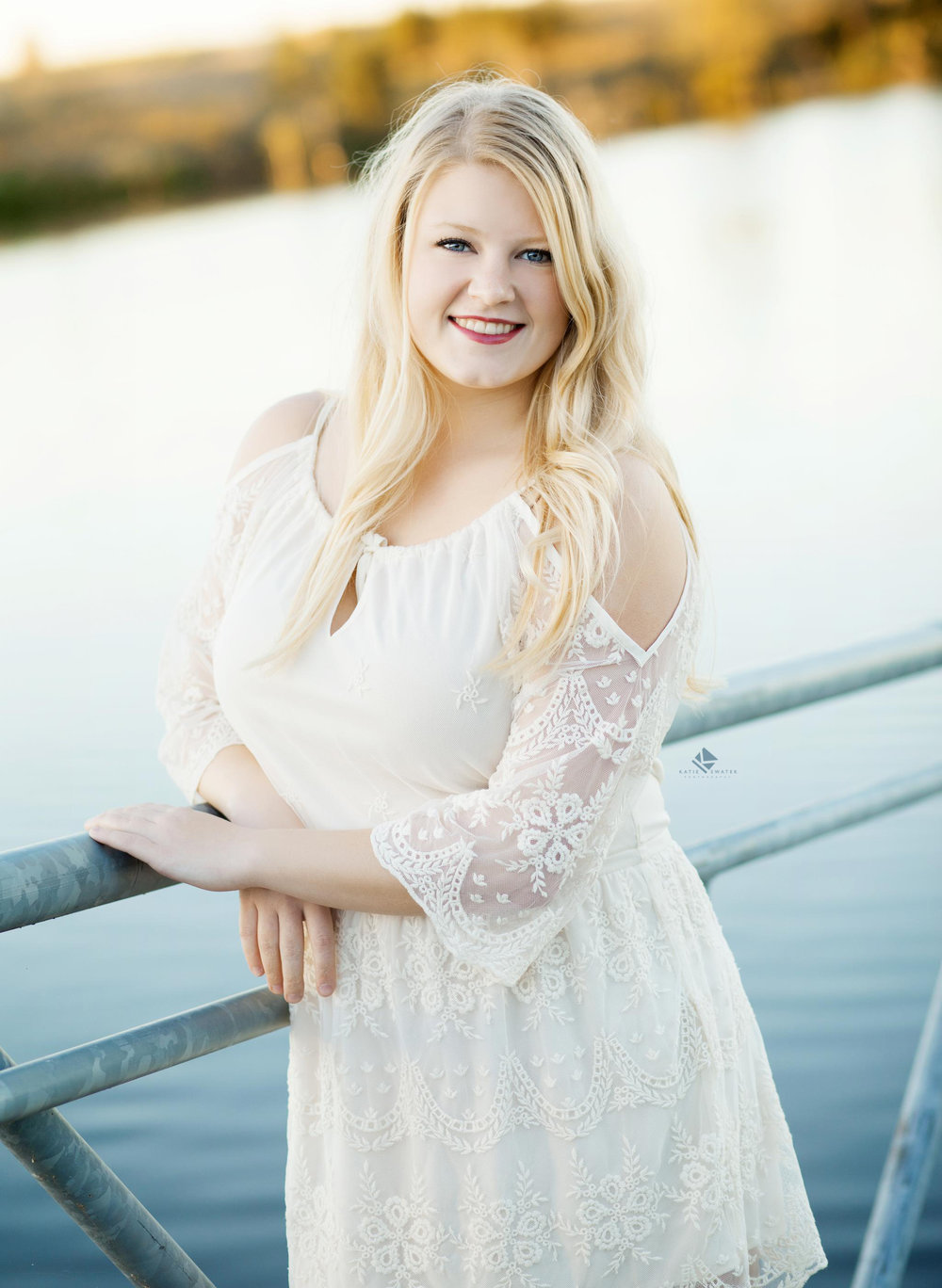 blonde senior girl in a white lace dress standing on a dock in the middle of lake in scotland sd