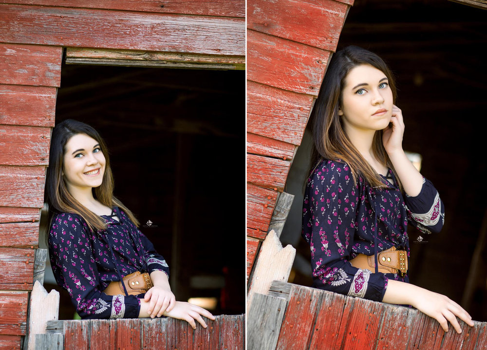 brunette senior girl in a blue paisley top posing in a red barn door window