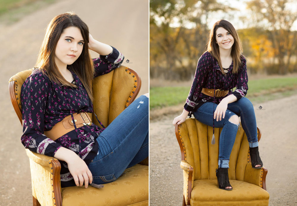 brunette senior girl in a blue, belted paisley top posing on a mustard colored chair on a gravel road in Nebraska