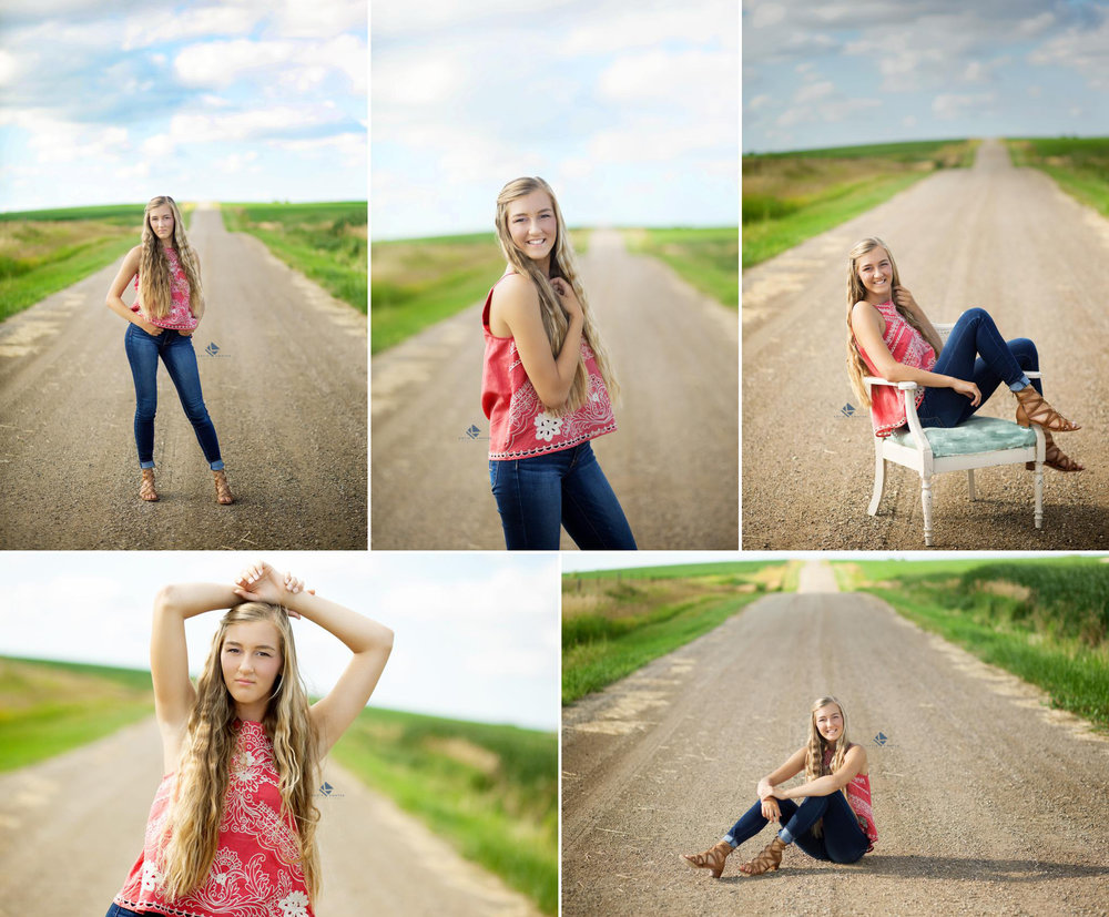 blonde senior girl in a red paisley top and dark denim jeans posing on a hilly gravel road with blue skies and clouds above