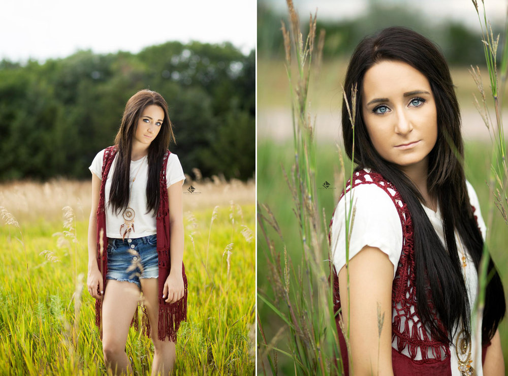 brunette senior girl in an ivory top and a rust colored vest with denim cut offs posing in a tall grass field for senior pictures