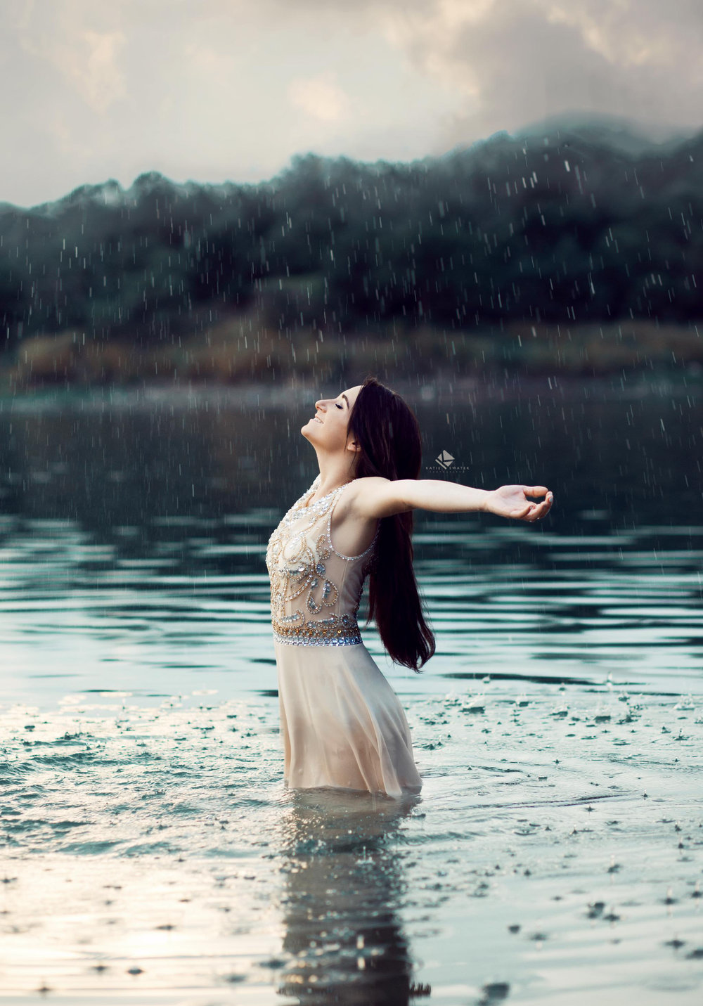 brunette senior girl in an ivory, beaded prom dress posing in the water while it rains