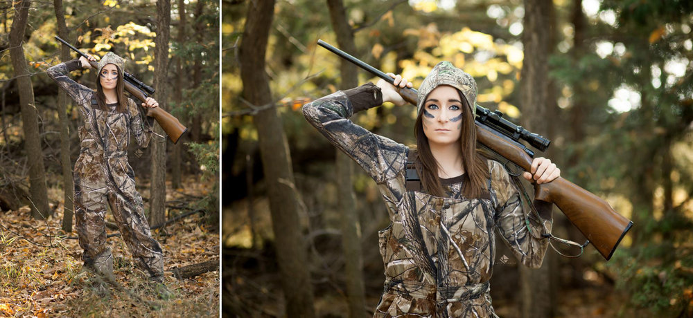brunette senior girl in camouflage bibs posing with a gun in a set of trees in the fall