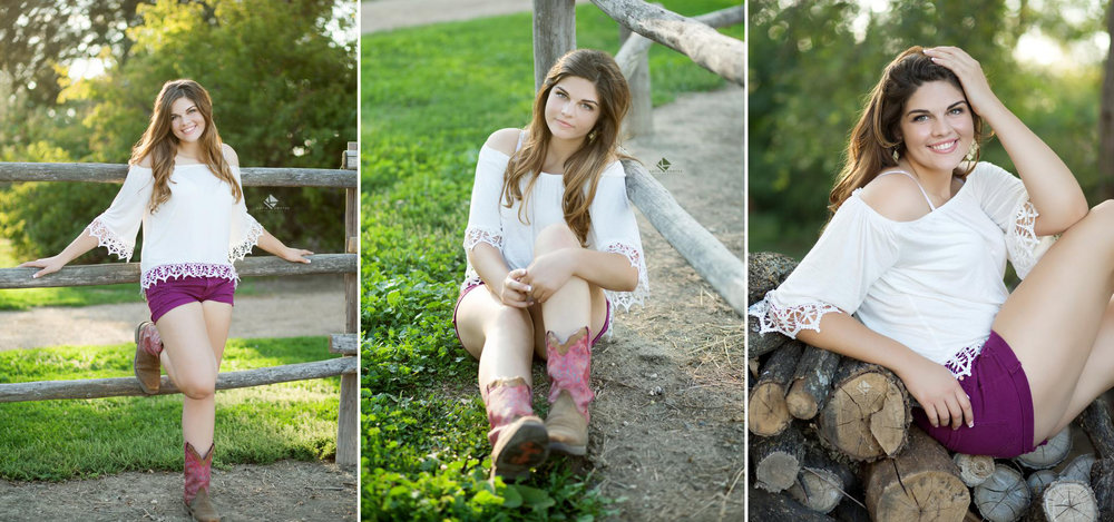 brunette senior girl in a white lace top and purple shorts with pink cowgirl boots posing next a wooden fence and on top of a wood pile
