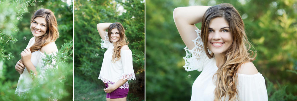 brunette senior girl in a white lace top and purple shorts posing in some evergreen trees for senior pictures
