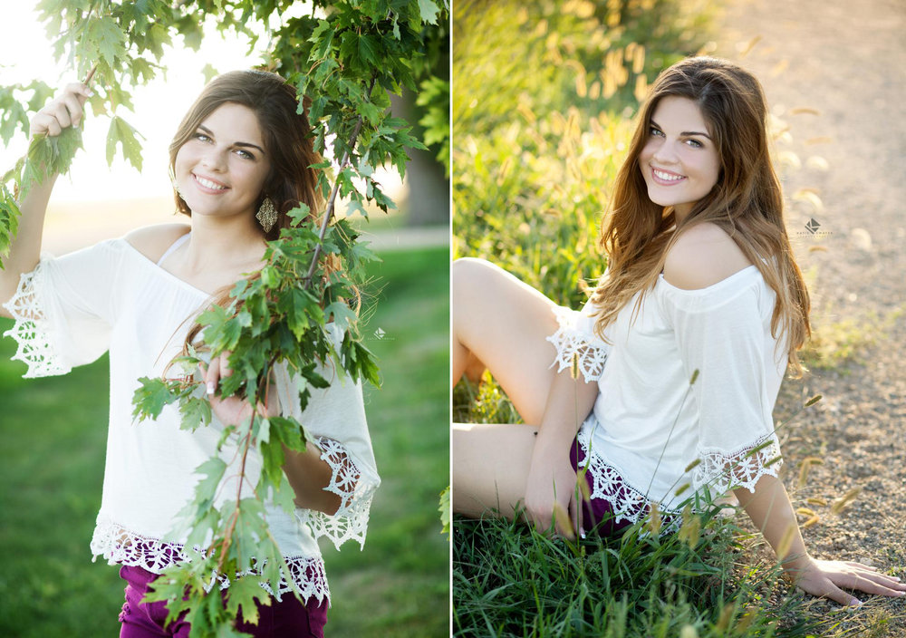 brunette senior girl in a white lace top and a pair of purple shorts peeking through a tree and sitting on a road in the evening summer light