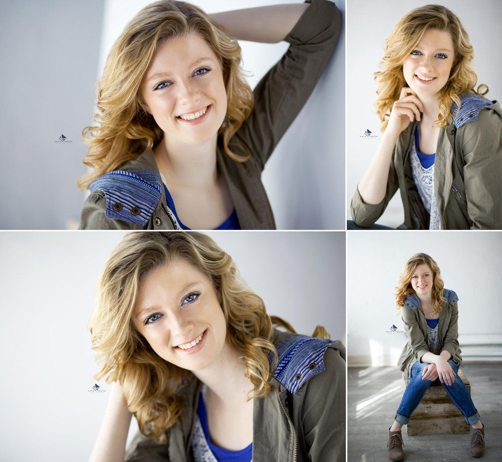 strawberry blonde senior girl in an olive jacket and jeans in a white studio set up