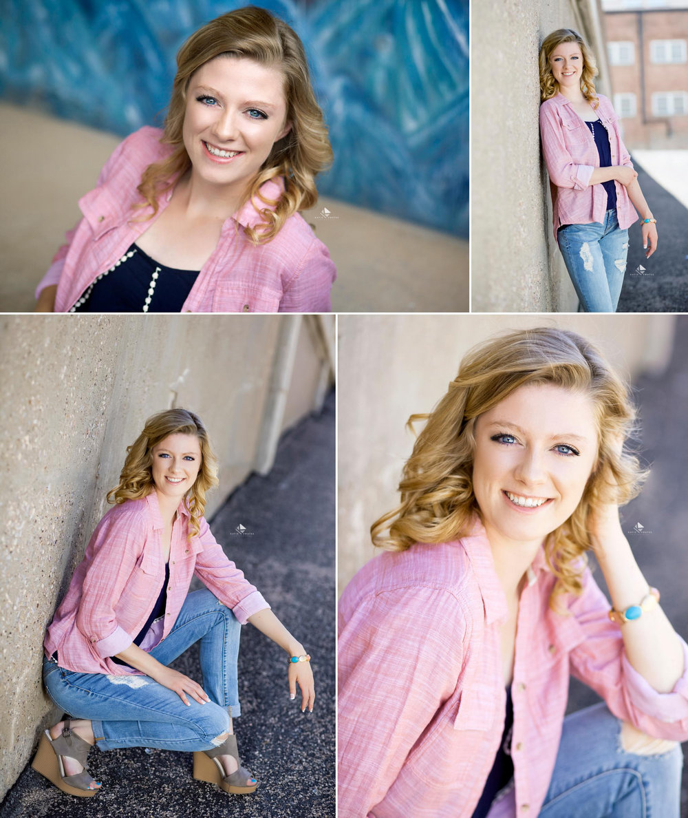 blonde senior girl in a navy blue tank top and pink button down sitting against a cement wall in Deadwood SD
