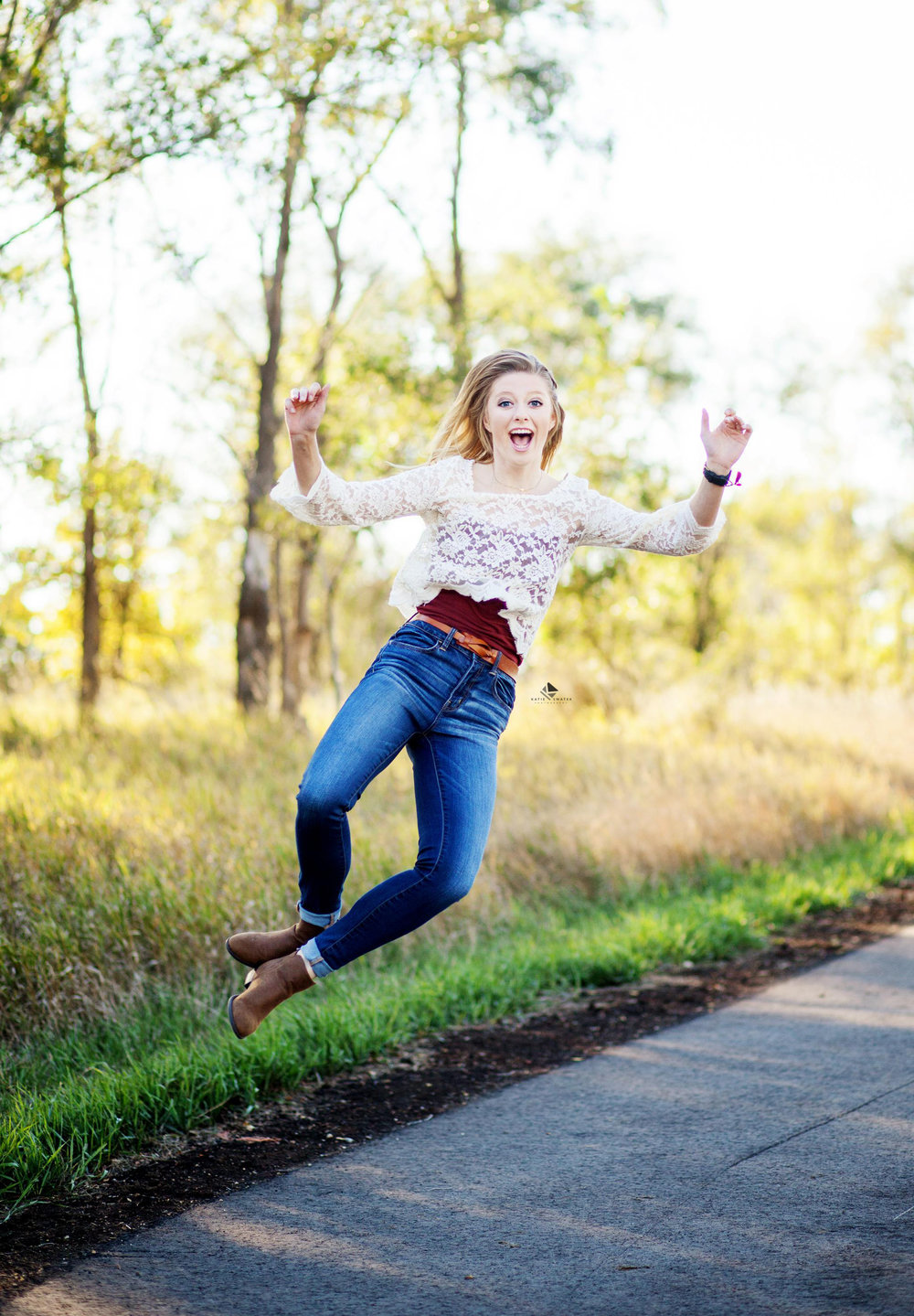 blonde senior girl in a white lace top and dark denim jeans jumping to click her heels midair on a walking path in the country