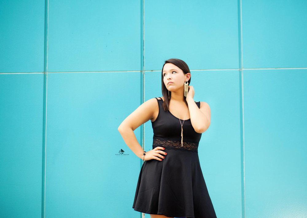 brunette senior girl in a black dress shooting senior pictures in front of a blue paneled building