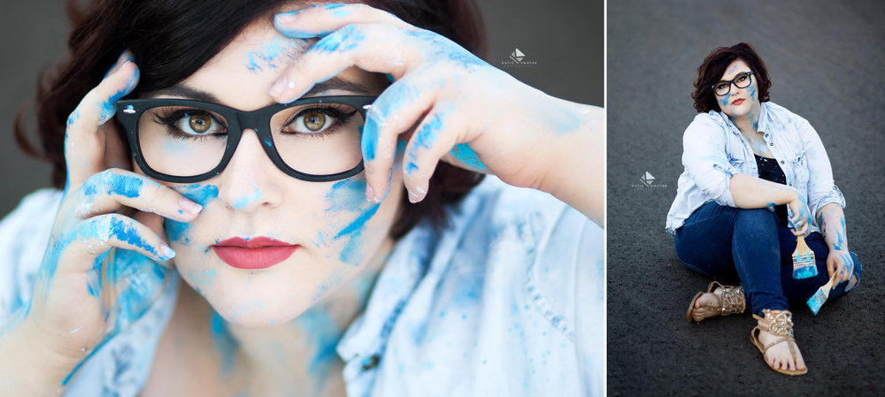 brunette senior girl in glasses with various shades of blue paint on her face and fingers poses for a senior picture to represent herself as an artist