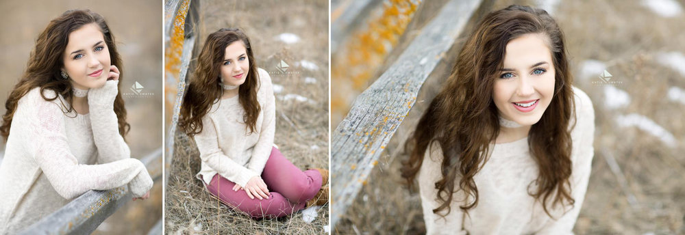brunette senior girl in a cream sweater and mauve jeans standing and sitting near a fence in the winter of South Dakota