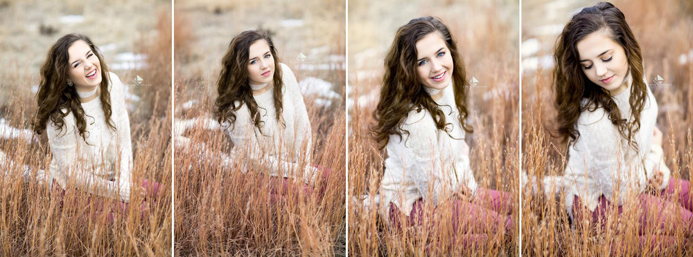 brunette senior girl in a cream colored sweater and mauve jeans sitting in a field of snow and and dead grass