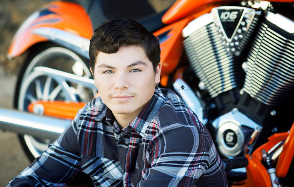 black haired senior boy in a button down sitting in front of his orange and chrome motorcycle