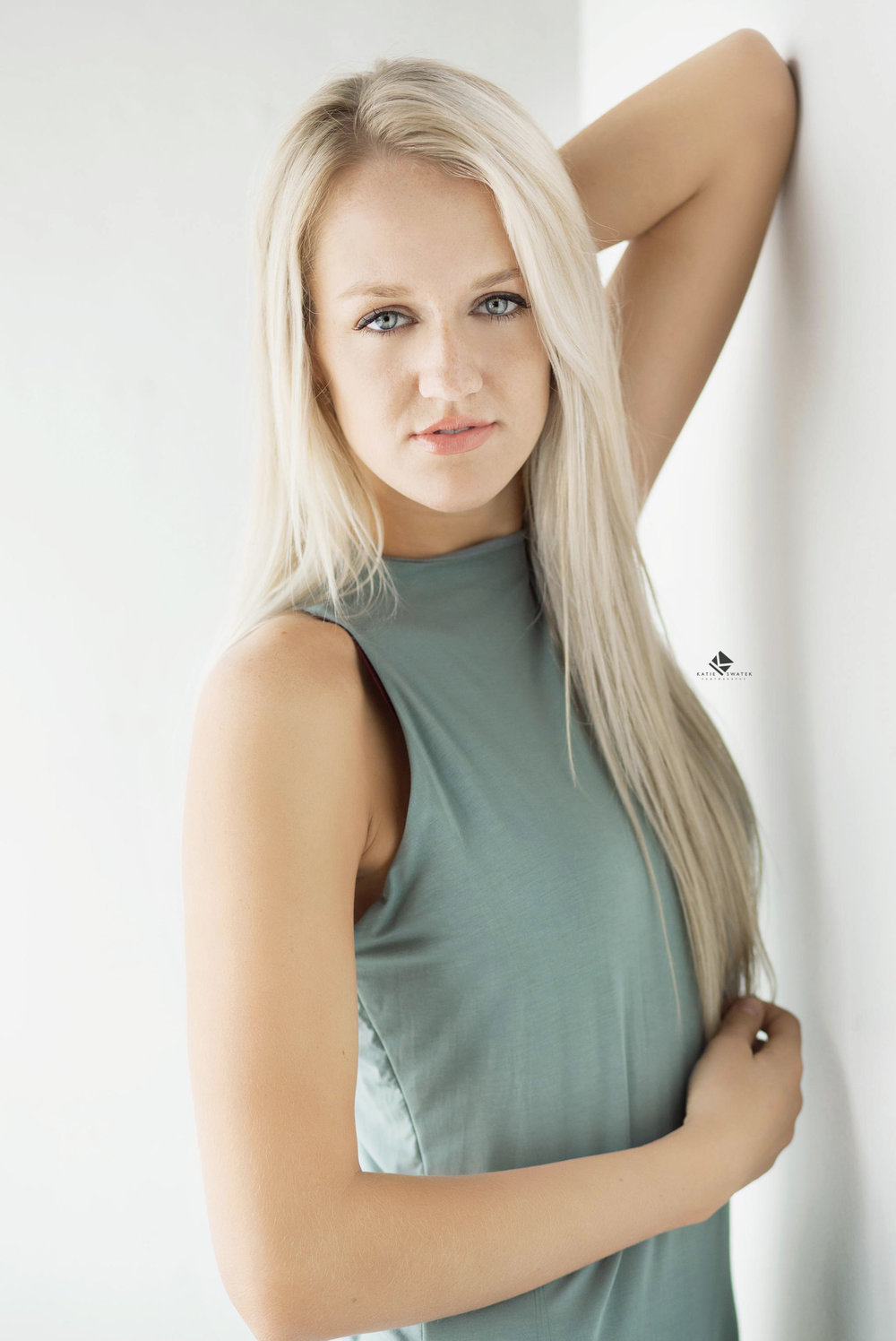 blonde senior girl in a sage green dress leaning against a white wall in a studio set up