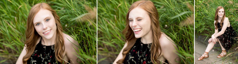 Red headed senior in black and red dress sitting in a green grassy area for senior pictures in South Dakota