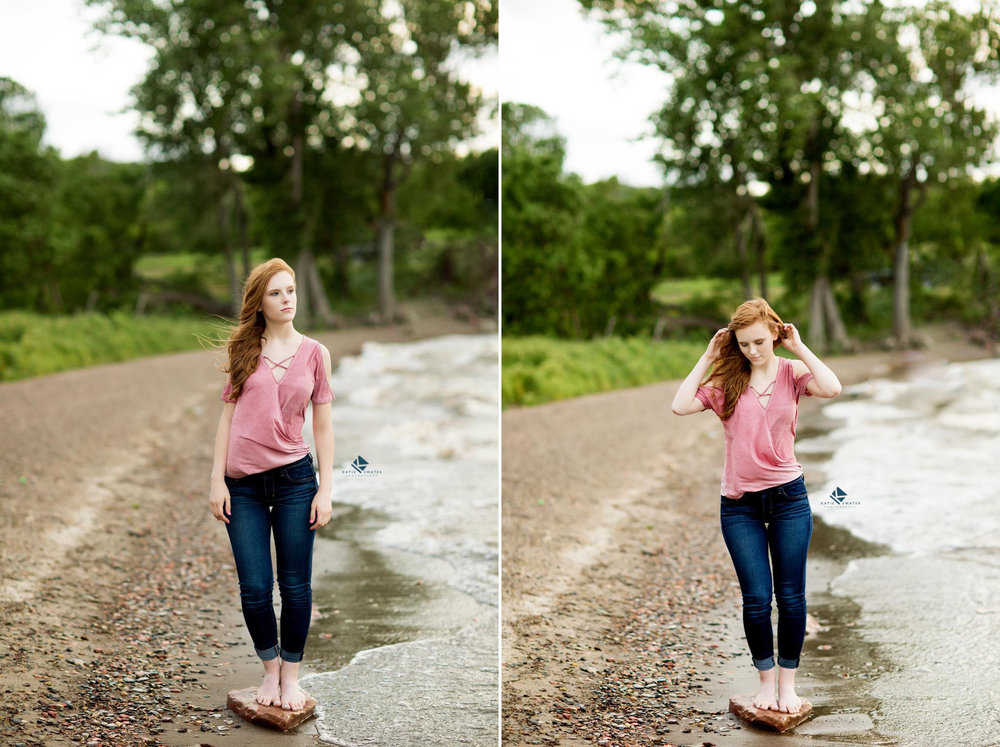 Red headed senior in a rose colored off the shoulder top and dark denim jeans on a rock and dirt beach near the shoreline of Lake Francis Case in South Dakota