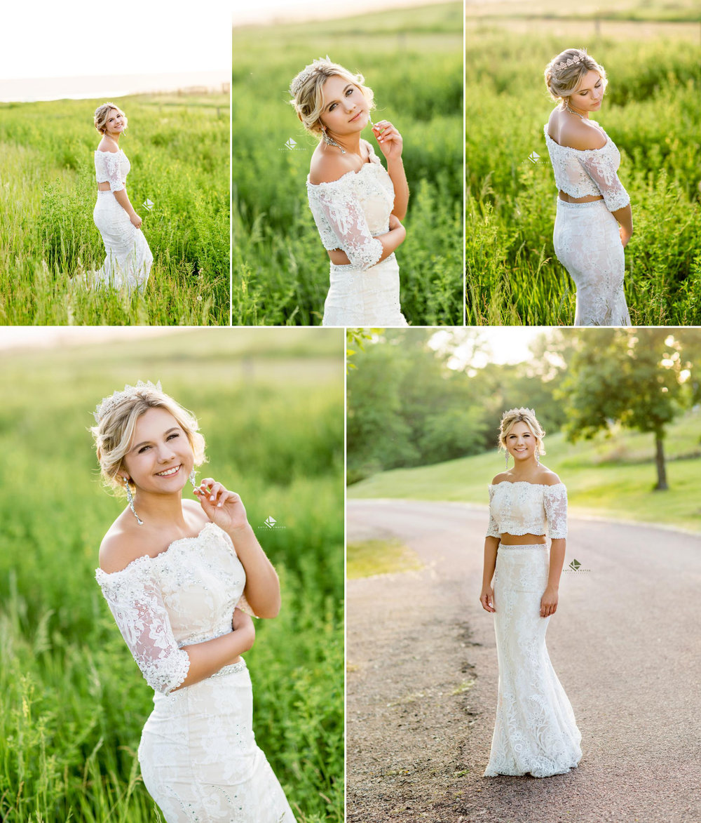 Blonde senior girl in a white lace, two piece prom dress walking through a field of green grass